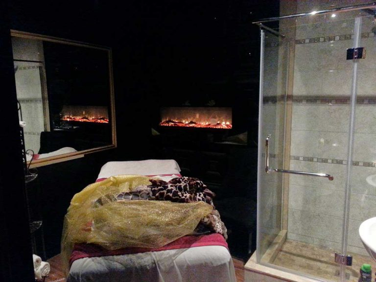 custom room with massage bed-build in fire place and shower build by refined renos aurora