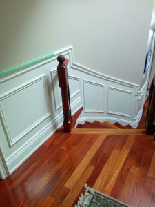 custom staircase with wainscoting wall trim and red wood floor - house renovation Toronto