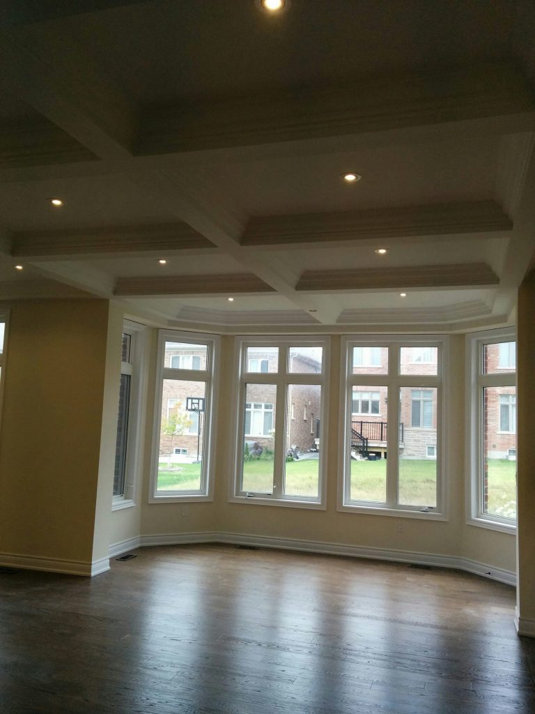 luxury coffered ceiling and bow window with baseboard trim in custom living room Aurora