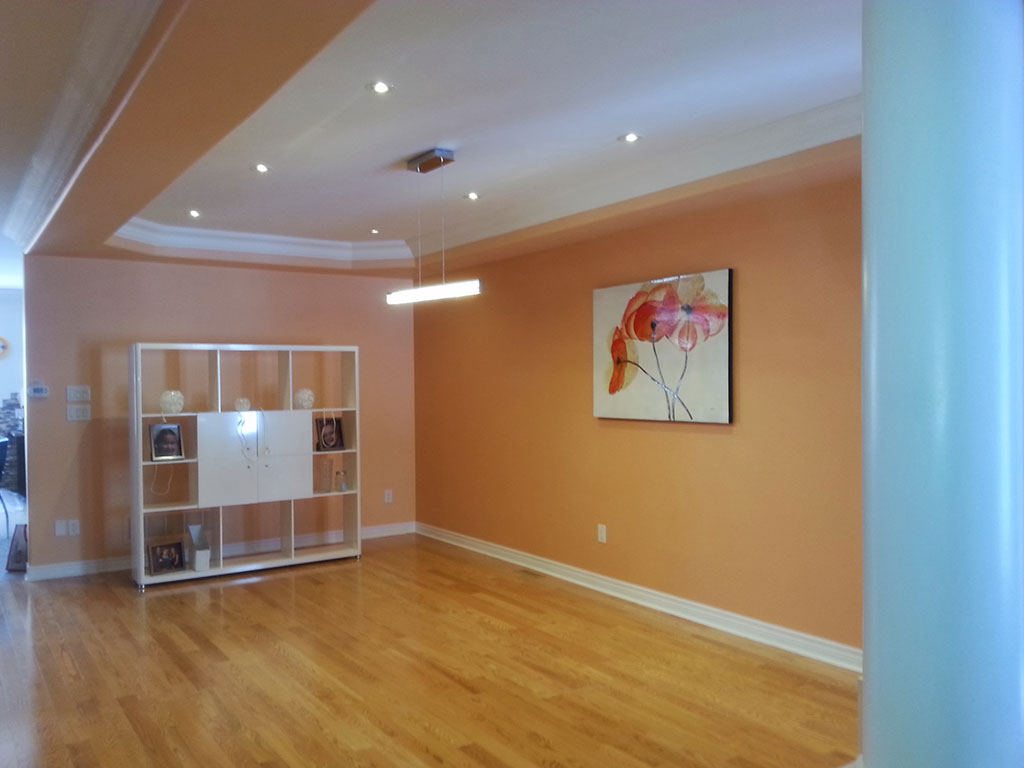 amazing family room with orange wall painting and ceiling crown moulding - house renovation