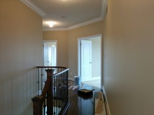 second floor hallway with beige wall painting and wooden stairs railings King city