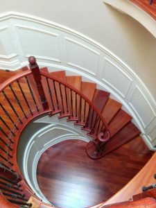 spiral stairs with red wood railings and wainscoting wall decor Bradford