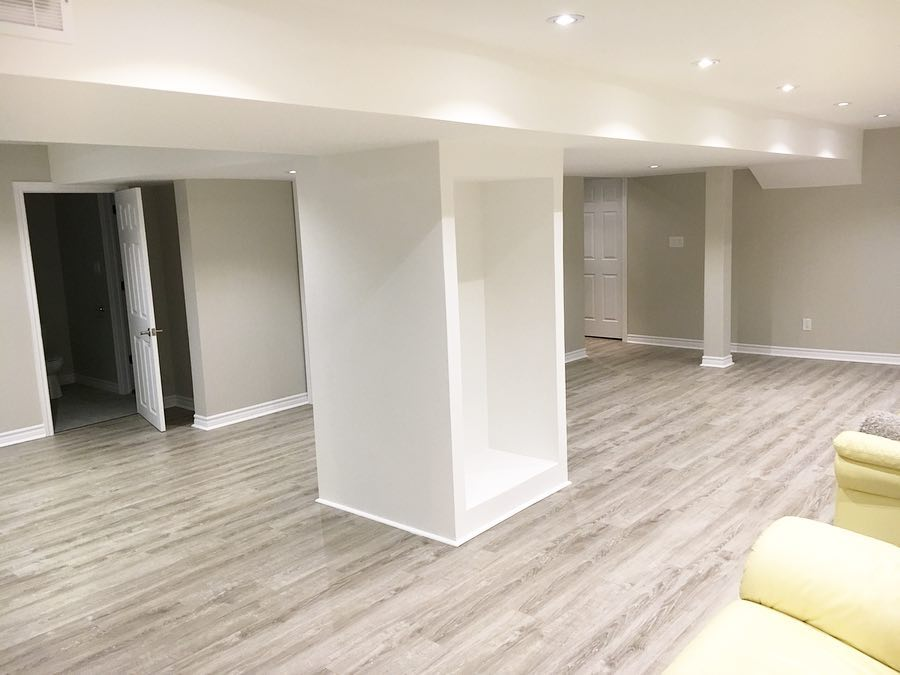 luxury basement living room with build in storage space and baseboard trim - house renovation