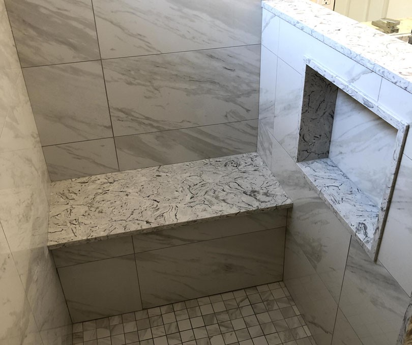 custom shower with marble tile decor and build in siting bench and storage space - bathroom remodel