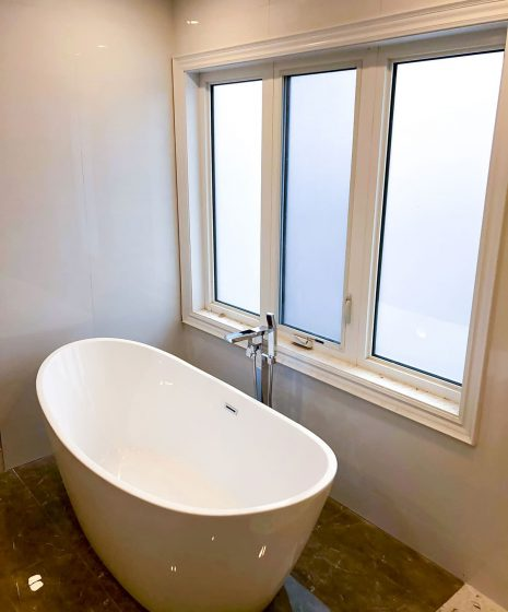 freestanding bathtub next to a window - bathroom renos
