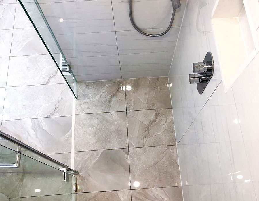 luxury walk in shower with build in storage space and tile floor - bathroom renovation